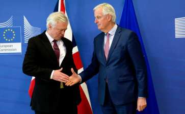 European Union chief Brexit negotiator Michel Barnier, right, reaches out to shake hands with British Secretary of State for Exiting the European Union David Davis prior to a meeting at EU headquarters in Brussels on Monday, March 19, 2018. (Virginia Mayo)